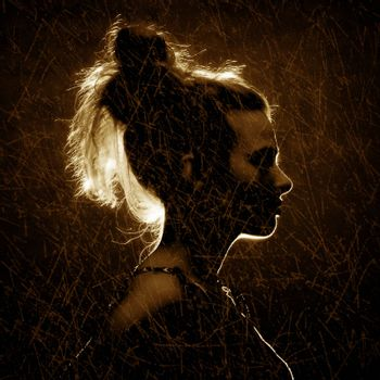 Silhouette of a beautiful young woman. Retro effect photo.