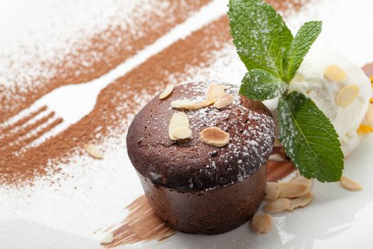 Warm dessert chocolate cake Fondant served on plate with ice-cream ball, almond chips, mint, icing, citron, cacao