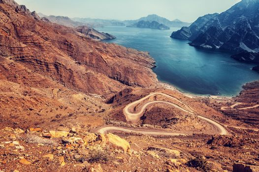 Beautiful landscape, curve road in dry arabian mountains over sea, exotic travel to the arab country, travel and tourism concept