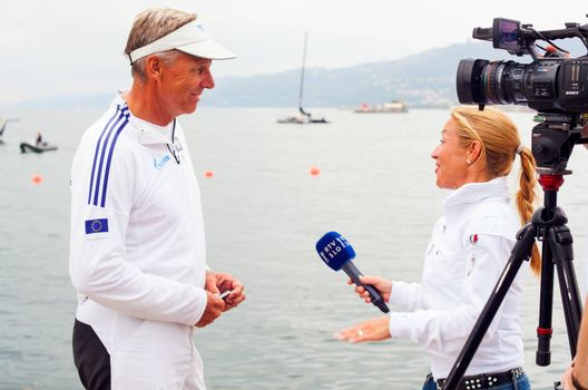 TRIESTE, ITALY - OCTOBER, 12: The journalist of the Slovenian tv, RTV interviewing Jochen Schuman skipper of the Esimit Europa 2, sailboat winner of  the 46 th Barcolana on October 12, 2014