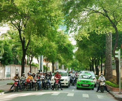 HO CHI MINH CITY, VIET NAM- OCT 7: Fresh air at Asian city, row of  tree on street, crowd of Vietnamese people on motorbike stop on street, group green trees with big trunk, Vietnam, Oct 7, 2014
