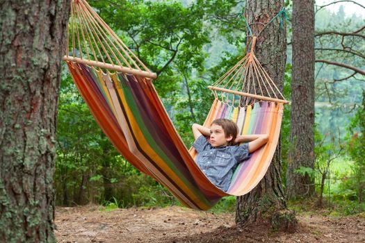 Serene boy lying in striped hammock in summer forest