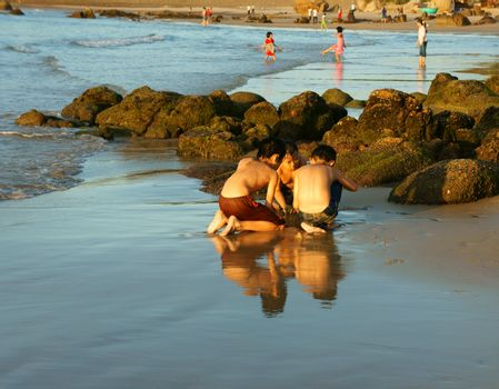 BINH THUAN, VIET NAM- OCT 25: Group of Asian kid playing together on beach, Vietnamese boy reflect on sand, scene of Co Thach seashore at yellow morning, children happy with vacation, Vietnam, 2014