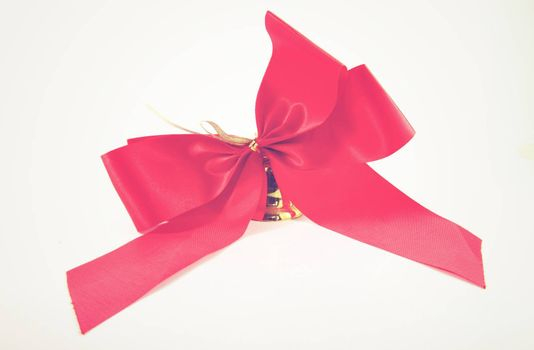 Red satin ribbon and golden bell with retro filter effect