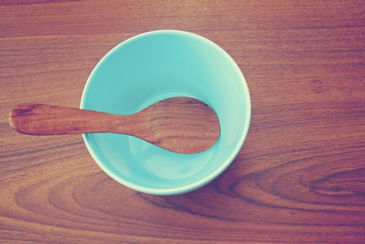 Blue bowl and wooden spoon on the table with retro filter effect