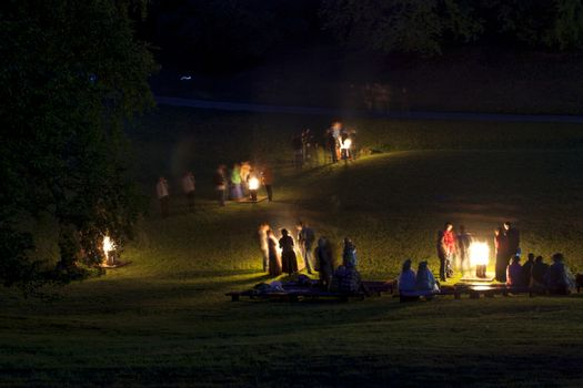 People celebrate summer solstice night around a bonfires in Latvian village. Midsumer or John's eve celebration around a bonfire is reminiscent of Midsummer's pagan rituals and very popular in Latvia.