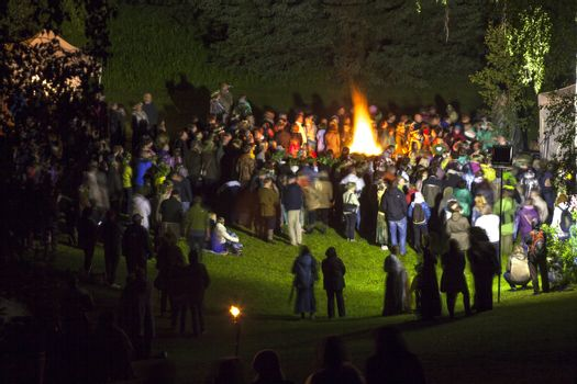 People celebrate summer solstice night around a bonfire in Latvian village. Midsumer or John's eve celebration around a bonfire is reminiscent of Midsummer's pagan rituals and very popular in Latvia.