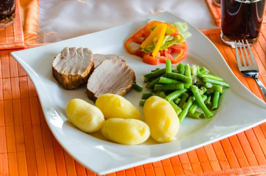 Fresh Schwenebraten with potatoes, green beans and salad.
