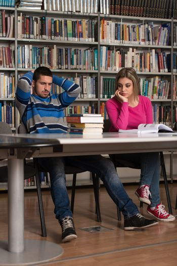 Confused Male Student Reading Many Books For Exam