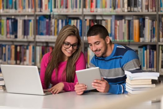 Couple Of Students With Laptop In Library