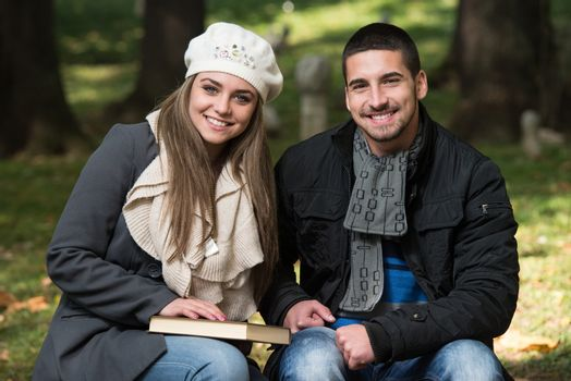 Young Romantic Couple In Park And Reading Book