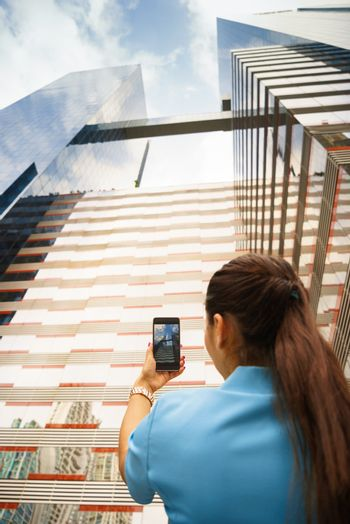 Person shooting photo of office building with telephone