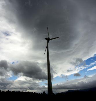 Wind turbine silhuette, with dark landscape background.