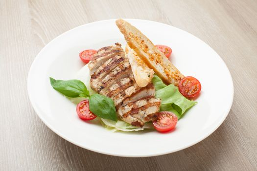 Gourmet delicious caesar salad with grilled beef meat fillet, romaine lettuce, cherry tomatoes,  cheese croutons and basil served in white plate