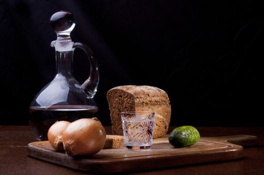 Still life of a decanter of vodka, two onions, cucumber and rye bread