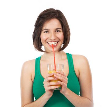 Portrait of a young woman drinking an orange juice with a straw, isolated on white