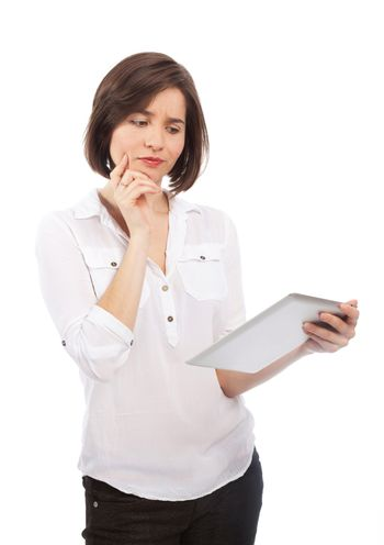 Young brunette holding and reading something on a touchpad with a wondering face, isolated on white