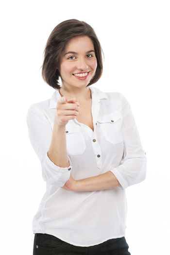 Portrait of a young brunette pointing in front of her,  isolated on white