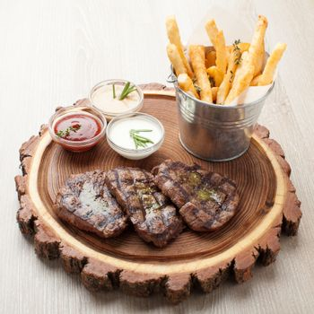 Portion of BBQ beef filet mignon steak  served  on wooden board with  ketchup, mustard and cream sauces, fried potatoes in aluminium bucket
