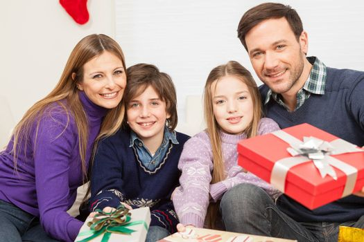 10-12, 30-35, 8-10, adult, boy, camera, caucasian, celebrating, celebration, child, children, christmas, colour, couple, daughter, enjoying, enjoyment, family, father, four, gift, gifts, girl, happiness, happy, holding, holiday, home, horizontal, house, indoors, interior, leisure, lifestyle, living, look, looking, love, loving, mature, men, model, mother, occasion, old, parent, people, present, presents, property, releases, room, sitting, smile, smiling, sofa, son, special, surprise, together, two, women, year, years
