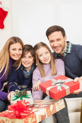 10-12, 30-35, 8-10, adult, boy, camera, caucasian, celebrating, celebration, child, children, christmas, colour, couple, daughter, enjoying, enjoyment, family, father, four, gift, gifts, girl, happiness, happy, holding, holidays, home, vertical, house, indoors, interior, leisure, lifestyle, living, look, looking, love, loving, mature, men, model, mother, occasion, old, parent, people, present, presents, property, releases, room, sitting, smile, smiling, sofa, son, special, surprise, together, two, women, year, years