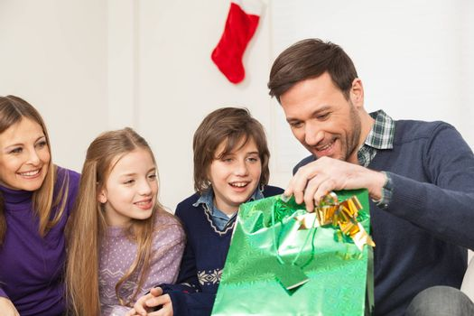 10-12, 30-35, 8-10, adult, at, boy, camera, caucasian, celebrating, celebration, child, children, christmas, colour, daughter, enjoying, enjoyment, family, father, four, gift, girl, happiness, happy, holding, holiday, home, horizontal, expresion, indoors, inside, living, look, looking, model, mother, occasion, old, parent, people, present, property, releases, room, sitting, smile, smiling, son, special, surprise, year, years, open, bag, green