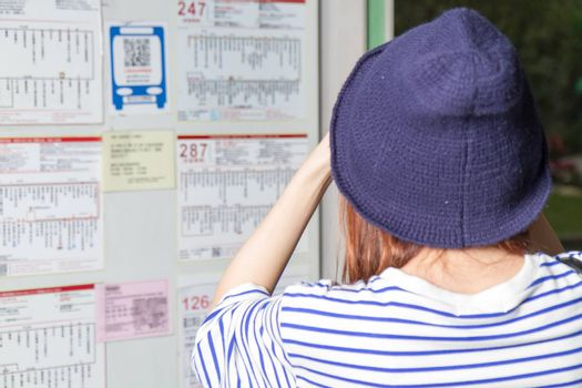 Woman waiting at bus stop in Taipei looking at bus timetable,p view from back of head