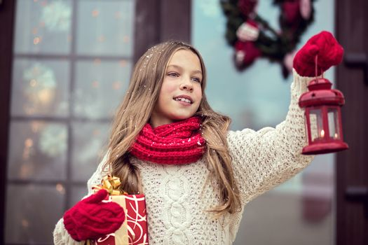Child girl welcome guests and holding presents, snow weather, house door is decorated before Christmas