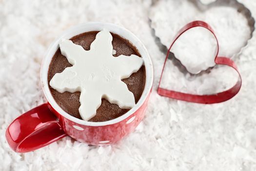 Above shot of a vibrant red cup of hot chocolate with snow flake shape of whipped cream. Extreme shallow depth of field.