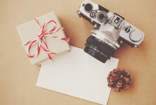 Handmade gift box and film camera on blank card with retro filter effect