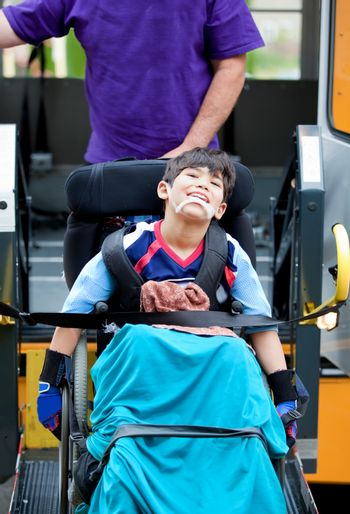 Disabled boy riding on school bus lift