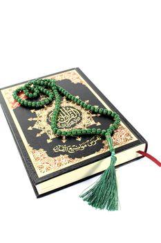 slammed Quran with green rosary
