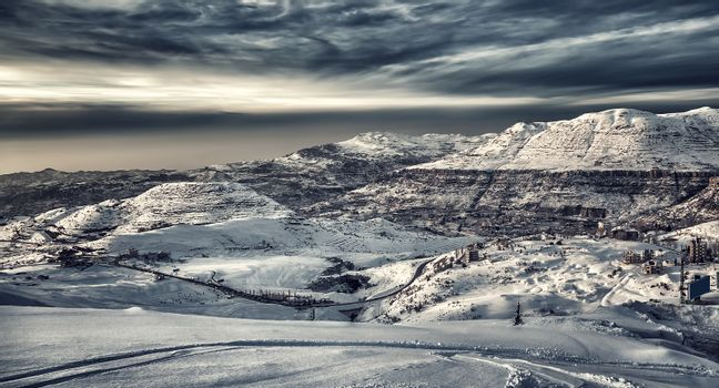Beautiful winter mountains landscape, mountain village covered with snow, ski resort on a cold dark day