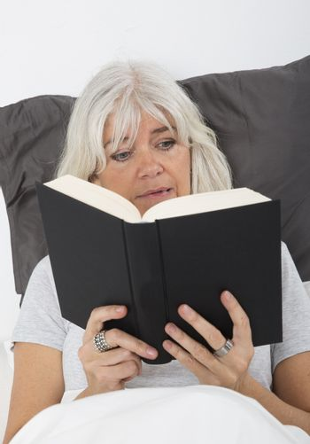 Mid age woman reading a nail-biting book in bed