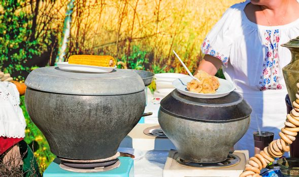 On the table are cooked in cast iron pots boiled corn, stewed potatoes, bagels, samovar to greet guests at the party under the open sky