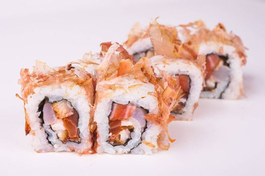 salmon sushi roll in tuna flakes isolated on white background