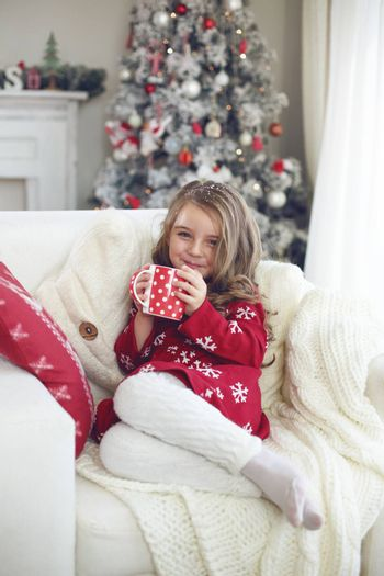5 years old little girl sitting on cozy chair and drinking milk near Christmas tree in morning at home