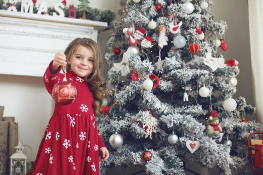 5 years old little girl decorating Christmas tree at home
