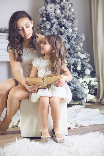 Mother with her child daughter dressed in beautiful fashion flower dress celebrating near Christmas tree