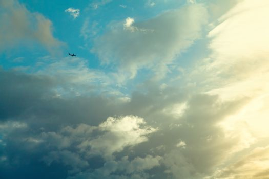 Airplane in the blue sky with clouds