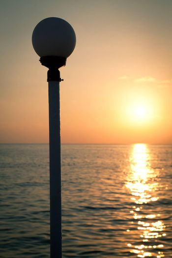 Golden sunset on a sea with silhouette of a lantern