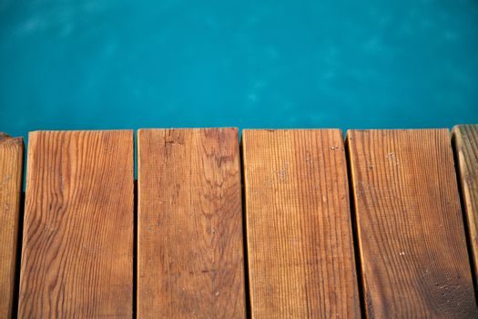 Closeup view of wooden pier with blue sea backdrop