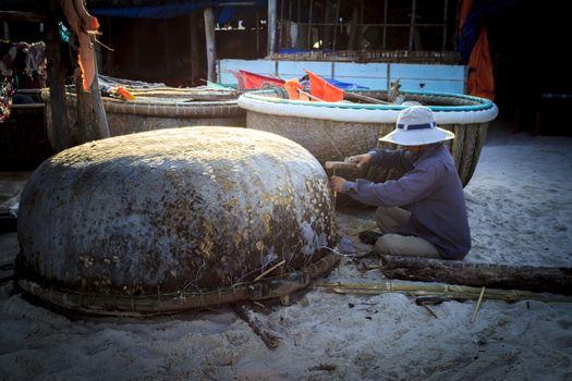 "Phu Quoc, Vietnam - November 2nd, 2013: the man was repairing his coracle in the ""Bai Kem"" beach, Phu Quoc, Vietnam"