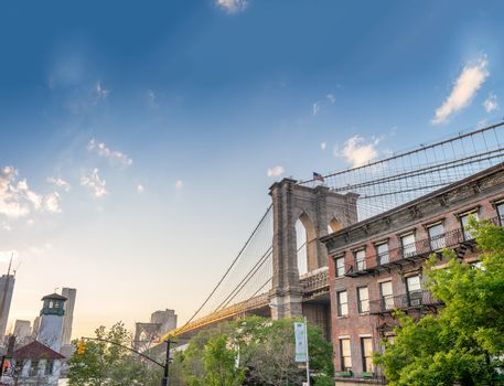 Brooklyn Bridge as seen from Brooklyn streets at sunset time.