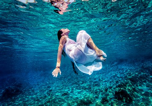 Gorgeous female dancing underwater