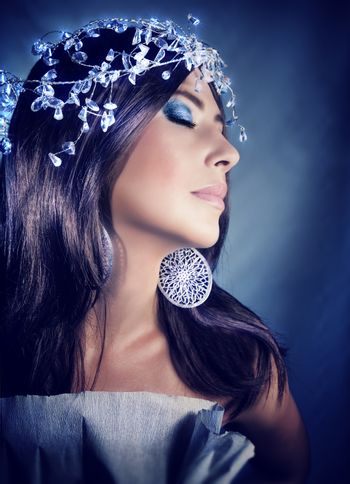 Closeup portrait of an attractive female with closed eyes and perfect festive makeup over blue background, wearing fashionable accessories, Christmas party concept