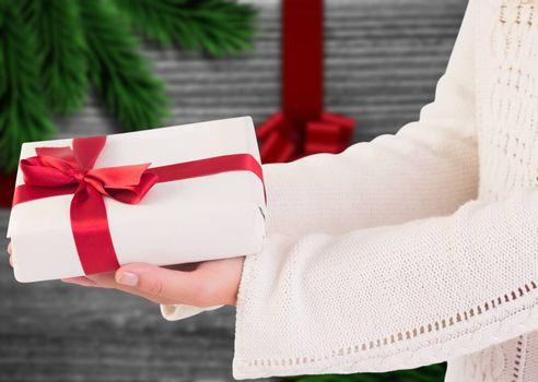 Woman offering a gift box against festive bow over wood