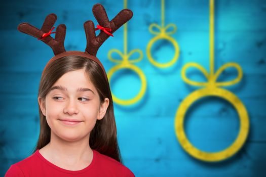 Composite image of festive little girl wearing antlers