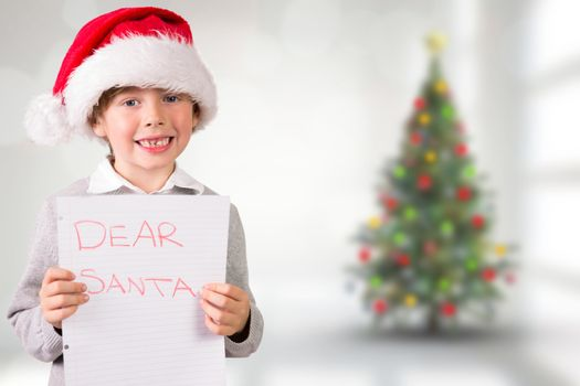 Festive boy showing letter against blurry christmas tree in room