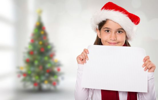 Festive little girl showing card against blurry christmas tree in room